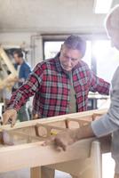 Male carpenters examining wood boat in workshop 11086035401| 写真素材・ストックフォト・画像・イラスト素材|アマナイメージズ