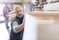 Male carpenter examining, touching wood boat in workshop 11086035402| 写真素材・ストックフォト・画像・イラスト素材|アマナイメージズ