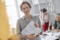 Portrait smiling businesswoman with paperwork in office meeting 11086035417| 写真素材・ストックフォト・画像・イラスト素材|アマナイメージズ