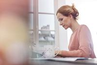 Serious, focused businesswoman working at digital tablet 11086035437| 写真素材・ストックフォト・画像・イラスト素材|アマナイメージズ