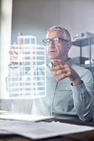 Male architect performing telekinesis, hovering futuristic glowing plastic model 11086035438| 写真素材・ストックフォト・画像・イラスト素材|アマナイメージズ