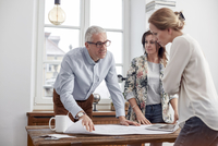 Architects reviewing, discussing blueprints in conference room meeting 11086035451| 写真素材・ストックフォト・画像・イラスト素材|アマナイメージズ