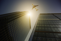 Airplane flying over highrise buildings, travel concept 11086035463| 写真素材・ストックフォト・画像・イラスト素材|アマナイメージズ