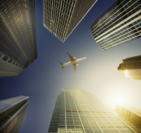Airplane flying in blue sky over highrise buildings, travel concept 11086035467| 写真素材・ストックフォト・画像・イラスト素材|アマナイメージズ