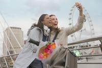 Enthusiastic, smiling women friends taking selfie with camera phone near Millennium Wheel, London, UK 11086035527| 写真素材・ストックフォト・画像・イラスト素材|アマナイメージズ