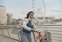 Portrait smiling woman bike riding on bridge over Thames River near Millennium Wheel, London, UK 11086035529| 写真素材・ストックフォト・画像・イラスト素材|アマナイメージズ