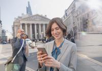 Businesswoman texting with cell phone on urban city street, London, UK 11086035530| 写真素材・ストックフォト・画像・イラスト素材|アマナイメージズ