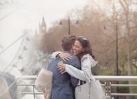 Smiling couple hugging, boyfriend surprising girlfriend with flowers on urban bridge, London, UK 11086035586| 写真素材・ストックフォト・画像・イラスト素材|アマナイメージズ