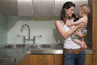 Woman holding baby in kitchen