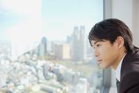 Businessman looking through window 11087000271| 写真素材・ストックフォト・画像・イラスト素材|アマナイメージズ