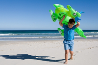 Little boy carrying inflatable dragon along beach