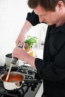 Man grinding pepper into saucepan
