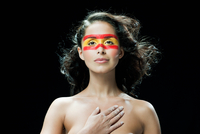 Woman with red and yellow face paint, hand on chest