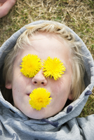 Sweden, Sodermanland, View of boy (10-11) with flowers on ey