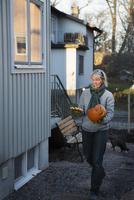 Sweden, Uppland, Stockholm, Bromma, Mature woman carrying carved pumpkin