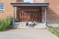 Sweden, Sodermanland, Nacka, Teenage girls (14-15) sitting in front of school door