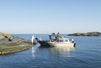 Sweden, Sodermanland, Stockholm Archipelago, Varmdo, Norsten, Family (14-15, 16-17) loading up boat at rocky beach