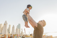 United Arab Emirates, Dubai, Man holding son (12-17 months) on beach
