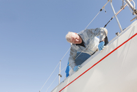 Sweden, Sodermanland, Jarna, Man maintaining sailboat