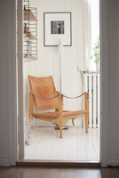 Sweden, Armchair in corner of white painted room seen through doorway