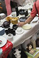 Sweden, Stockholm, Normalm, Blasieholmstorg, Senior woman reaching for tableware item on stall at flee market