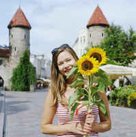 Estonia, Tallinn, Portrait of young woman holding sunflowers