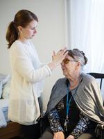 Finland, Helsinki, Female caregiver doing hair of senior woman