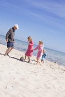 Sweden, Gotland, Faro, Skalasand, Grandfather playing volleyball on beach with his grandchildren (2-3, 8-9, 10-11)