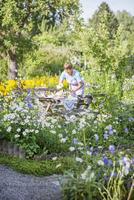 Sweden, Skane, Woman setting table in garden
