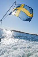 Sweden, Swedish West Coast, Bohuslan, Karringon, Boat with Swedish flag on sea