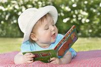 Sweden, Bohuslan, Tjorn, Cute girl (18-23 months) looking at book