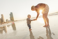 United Arab Emirates, Dubai, Woman with son (12-17 months) on beach at sunset