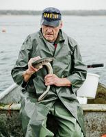 Sweden, Skane, Yngsjo, Fisherman holding eel