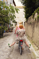 France, Languedoc-Roussillon, Peyriac de Mer, Two women riding bicycle together