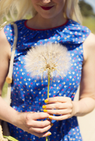 France, Woman holding dandelion