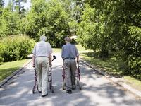 Finland, Esbo, Two senior men with walking frames walking away