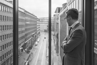Finland, Helsinki, Businessman looking through window