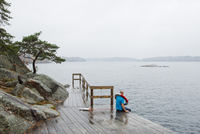 Sweden, Stockholm Archipelago, Sodermanland, Lillsved, Man sitting on pier and looking at Baltic Sea