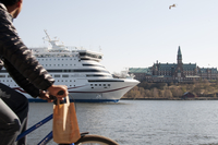 Sweden, Stockholm, Djurgarden, Man riding bike and looking at ferry