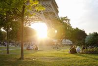 France, Ile-de-France, Paris, People in park by Eiffel Tower at sunset