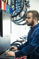 Finland, Mechanic in bike shop using computer