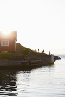 Sweden, Stockholm Archipelago, Sodermanland, Landsort, Oja, Red cottage on coast of Baltic sea at sunset