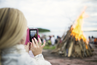 Finland, Nyland, Helsinki, Drumso, Woman photographing bonfire with her smartphone