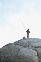 South Africa, Cape Town, Camps Bay, Man fishing on rock