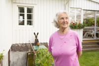 Sweden, Ostergotland, Finspang, Senior woman smiling in backyard