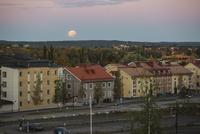 Sweden, Vasterbotten, Umea, Moon over residential district