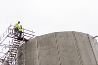 Sweden, Vastmanland, Man and woman standing on scaffolding by water treatment plant