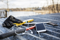 Sweden, Uppland, Rindo, Work tools and smart phone on metal roof