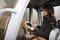 Sweden, Uppland, Nacka, Woman using digital tablet in bulldozer