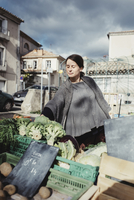 France, Languedoc-Roussillon, Sauve, Young tourist choosing vegetables on market